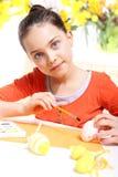 La fille décore des oeufs de pâques Photographie stock libre de droits