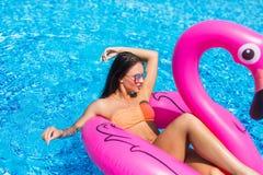 La fille de beauté s'assied sur les flamants gonflables de matelas dans la piscine et a l'amusement Réception de regroupement Images stock