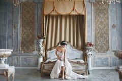La fille de beauté, sexy et à la mode étonnante de brune de modèle, portant dans la robe de dentelle, s'assied sur le lit image libre de droits