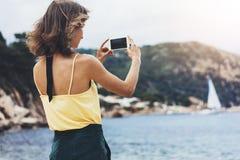 La fille de blogger de hippie tient le téléphone portable dans des mains femelles, prennent la photo de photo du paysage marin na photographie stock libre de droits