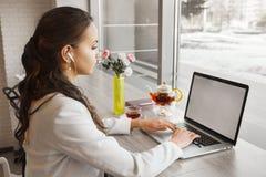La fille de brune avec des écouteurs écoute et dactylographiant sur l'ordinateur portable photo libre de droits
