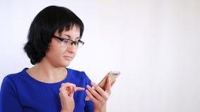 La fille de brune avec des verres utilise un smartphone sur un fond blanc Le doigt de fille touche le smartphone utilisant le con banque de vidéos