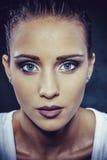 La fille de brune avec le beau maquillage et a mouillé dans un pulvérisateur de l'eau Image stock