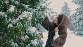 La fille de brune dans le manteau de fourrure brun balaye la marche dans le mouvement lent d'horaire d'hiver clips vidéos