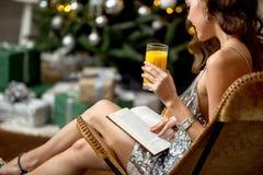 La fille de brune dans une robe ?galisante grise brillante tenant un verre de jus s'assied dans un fauteuil de concepteur ? c?t?  image stock