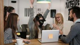 La fille de brune essaye l'APP pour des verres de réalité virtuelle de casque de VR ses amis et collègues la soutenant dans le bu Photos stock