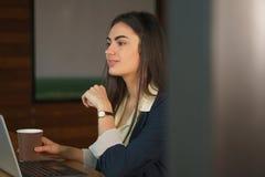 La fille de brune de portrait avec un ordinateur portable et un café pense avant de prendre une décision importante Images stock