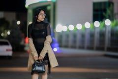 La fille de brune pose contre la ville ?galisante de nuit, les lumi?res color?es illuminent les fen?tres de achat images stock
