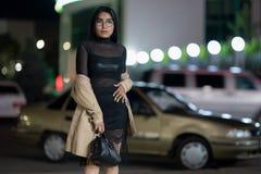 La fille de brune pose contre la ville ?galisante de nuit, les lumi?res color?es illuminent les fen?tres de achat image libre de droits