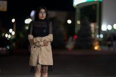 La fille de brune pose contre la ville ?galisante de nuit, les lumi?res color?es illuminent les fen?tres de achat photo stock