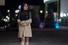 La fille de brune pose contre la ville ?galisante de nuit, les lumi?res color?es illuminent les fen?tres de achat photographie stock libre de droits