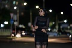 La fille de brune pose contre la ville ?galisante de nuit, les lumi?res color?es illuminent les fen?tres de achat photos libres de droits