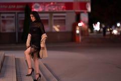La fille de brune pose contre la ville ?galisante de nuit, les lumi?res color?es illuminent les fen?tres de achat image stock