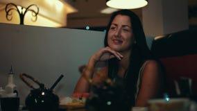 La fille de brune s'asseyent à la table dans le restaurant de sushi Rire Entretien avec quelqu'un clips vidéos