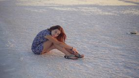 La fille de calme appréciant le soleil, s'assied au sol couvert du sel près du lac banque de vidéos