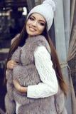 La fille de charme avec les cheveux droits foncés utilise le manteau de fourrure luxueux et le chapeau tricoté Photographie stock libre de droits