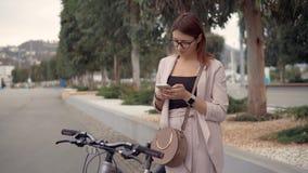 La fille de charme est lisante et envoyante des messages, se tenant dehors dans la ville banque de vidéos