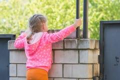 La fille de cinq ans montée sur la barrière de brique et le recherche Images libres de droits