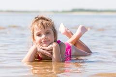 La fille de cinq ans se situe dans l'eau dans le bas-fond de la rivière photos stock