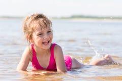 La fille de cinq ans se situe dans l'eau dans le bas-fond de la rivière, riant et regardant vers la gauche image libre de droits