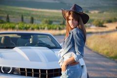 La fille de cowboy se tient au convertible Images stock