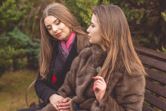 La fille de deux amis portent les manteaux chauds d'hiver Photo stock