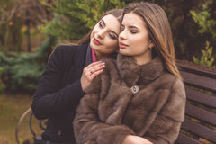 La fille de deux amis portent les manteaux chauds d'hiver Photos stock