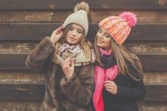 La fille de deux amis portent les vêtements chauds d'hiver Image libre de droits