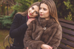 La fille de deux amis portent les vêtements chauds d'hiver Images stock