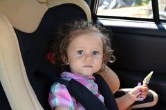 La fille de deux ans s'assied dans la voiture dans un siège de voiture de bébé Images libres de droits