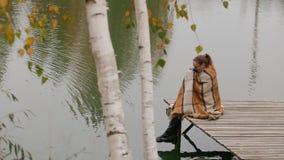 La fille de femme s'asseyent sur le banc en bois sous le mouvement de branche de saule en vent près du lac banque de vidéos