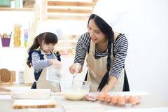 La fille de fille de mère et d'enfant font cuire des biscuits et ont l'amusement Photo stock