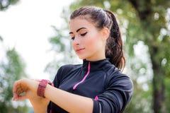 La fille de Ftitness place le traqueur de chronomètre sur son poignet pendant la course Photographie stock
