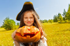La fille de Halloween dans le costume du pirate tient le potiron Image libre de droits
