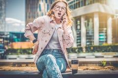 La fille de hippie repose extérieur, éprouvant des douleurs de dos et entraînant l'aide au téléphone La femme parle au téléphone  photographie stock libre de droits
