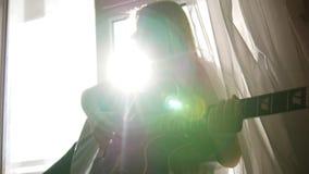La fille de jeune adolescent jouant la guitare acoustique à la maison, se ferment  banque de vidéos