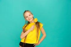 La fille de l'adolescence avec la lucette colorée sur un fond bleu Image libre de droits