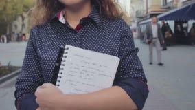 La fille de l'adolescence d'école tenant le livre d'exercice et va à la rue de ville banque de vidéos