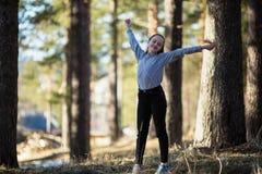 La fille de l'adolescence d'amusement mignon dupe autour en parc de pin photographie stock