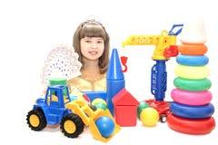 La fille de l'adolescence dans la belle robe et des jouets colorés lumineux sur un blanc a isolé le fond Photo libre de droits