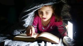 La fille de l'adolescence de lecture d'enfant lit le chien de livre la nuit avec la lampe-torche se trouvant sous une couverture banque de vidéos
