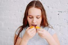 La fille de l'adolescence a deux macarons immédiatement, le concept de l'obésité et de manger avec excès d'enfance photos libres de droits
