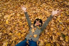 La fille de l'adolescence en parc d'automne se trouve sur le feuillage Images libres de droits