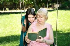 La fille de l'adolescence et sa grand-mère ont lu un livre en parc horizontal Photographie stock