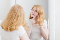 La fille de l'adolescence examine l'acn? devant le miroir photos stock