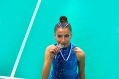 La fille de l'adolescence de gymnastique de médaillé tient la médaille photographie stock libre de droits