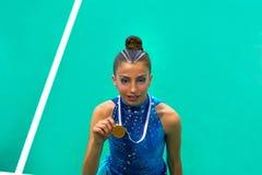 La fille de l'adolescence de gymnastique de médaillé tient la médaille image libre de droits