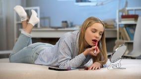 La fille de l'adolescence mettant sur le rouge à lèvres rouge de mères, désir adulte de regard, améliorent l'aspect photos stock