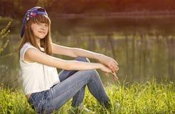 La fille de l'adolescence mignonne s'assied sur une herbe près du lac Photos libres de droits
