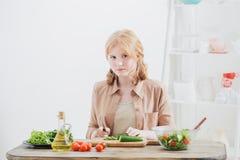 La fille de l'adolescence prépare la salade à la maison image libre de droits